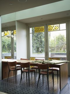The space was extended on the garden side to create a summer dining room. The cement-tile floor extends out to the garden terrace, so with the doors pulled back, the room becomes part of the garden. An inherited Murano chandelier, Murano glass wall lights, and colored, patterned glass panels salvaged from a church soften the otherwise stark modern space.