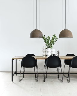 Morten Bo Jensen, of Danish industrial design company Vipp, and his partner, graphic designer Kristina May Olsen, have mixed repurposed vintage items with their own creations inside their Copenhagen apartment. In the kitchen, the dining table—Jensen's first piece for Vipp—is made of a powder-coated aluminum frame with a recycled, untreated teak top. The lamps overhead are salvaged and rewired Copenhagen streetlights.
