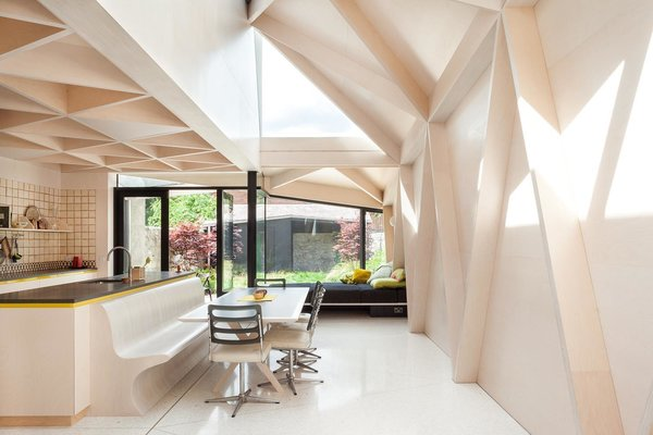 Abutting the kitchen, the owners' existing dining chairs, table, and bench have found a new home beneath the extension's glass planes and plywood structure. Reflective white Terrazo floors further accentuate the airiness of the open-concept extension.