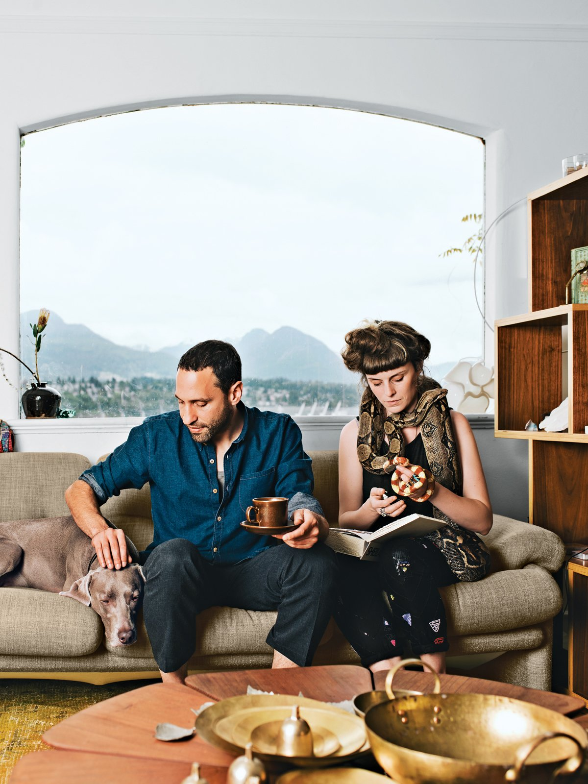 """Living Room, Sofa, Coffee Tables, Bookcase, Shelves, Storage, and Rug Floor In the living room of their Vancouver home, Omer Arbel and Aileen Bryant sit on a Coronado sofa by Afra and Tobia Scarpa for B&B Italia. They are joined by their Weimaraner, Bowie, boa constrictor, Picasso, and milk snake, Legs.  """"I have a casual approach to prototyping that involves our day-to-day life. I am always tinkering, and I have lots of transformers to run electricity through things, but Aileen lives with me now, so I have to be respectful. Before she moved in it was like a total madhouse; now I can't pour concrete in the kitchen. It is a collaboration in a sentimental sense. This work is my life, and the objects are my objects, but how they are arranged and the flow of each room are something we've created together here.""""  127+ Inspiring Interior Ideas from Love Animals? This House is for You"""
