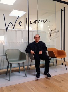 "Designer Boris Berlin with his Fiber Chairs at Muuto's showroom in central Copenhagen.   Of the Iskos-Berlin design, which carries on a strong modern tradition influenced by the Eames shell chair, Berlin says, ""One of the most difficult and noble disciplines is to design without eccentricity."" The chair's supernormal silhouette translates to different uses with four different bases (powder coated steel, sled, swivel, and wood), while the seat portion is 100% recyclable thanks to its eco-friendly composite mix using 25% wood fibers, 70% PP (polyproplene) and 5% coloured polyproplene."