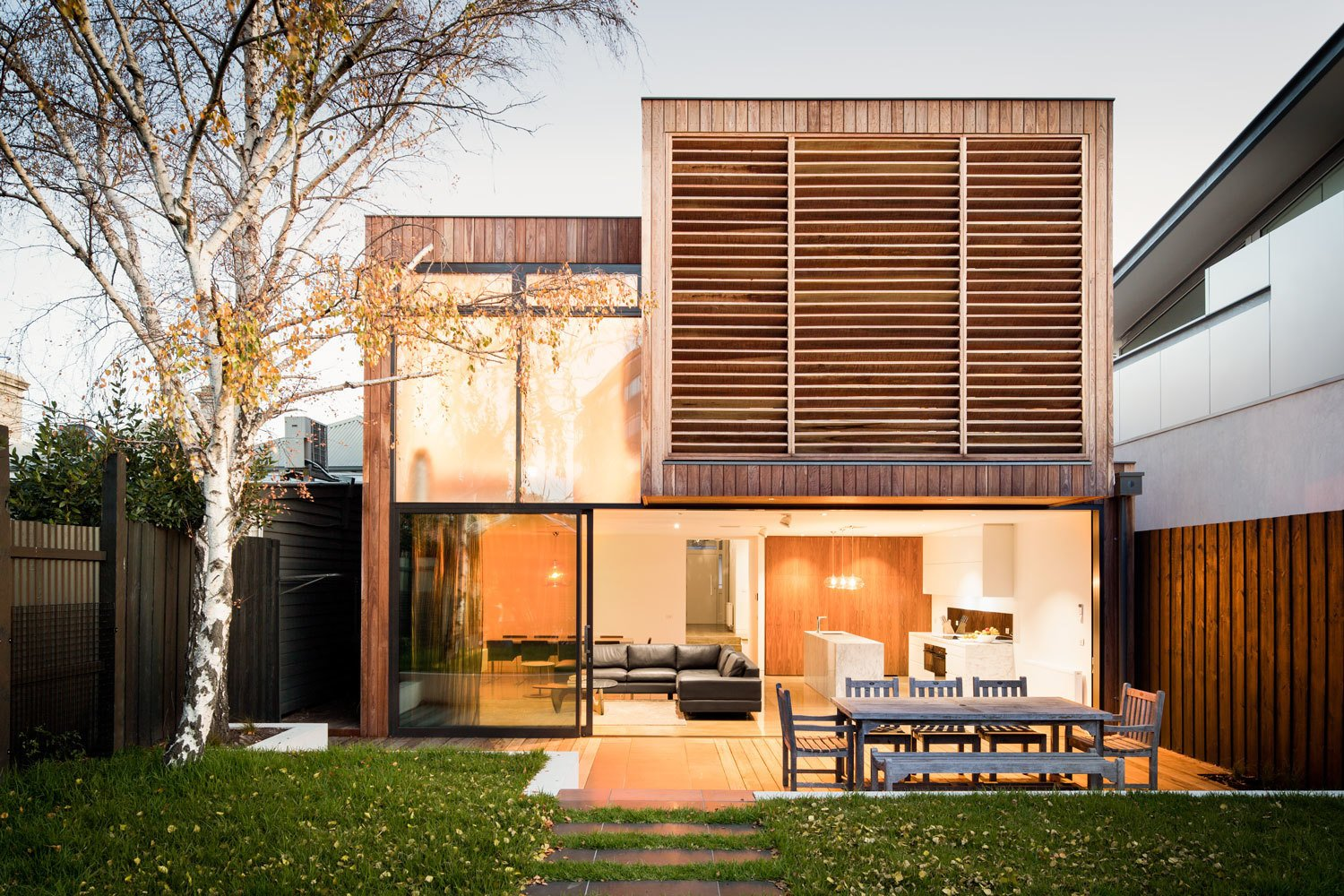 Outdoor, Back Yard, Grass, Trees, Walkways, Wood Fences, Wall, Vertical Fences, Wall, Small Patio, Porch, Deck, and Wood Patio, Porch, Deck The family members, who are active and spend ample time at the beach, requested the feel of a seaside retreat. The architects accomplished this with Ironbark wood slats on the exterior—the Australian hardwood is incredibly durable and will weather silver-grey over time. The wooden louvers shade a large playroom that's adjacent to the boy's bedrooms.  A Breezy Modern Addition Opens Up a Historic Melbourne Home by Zachary Edelson