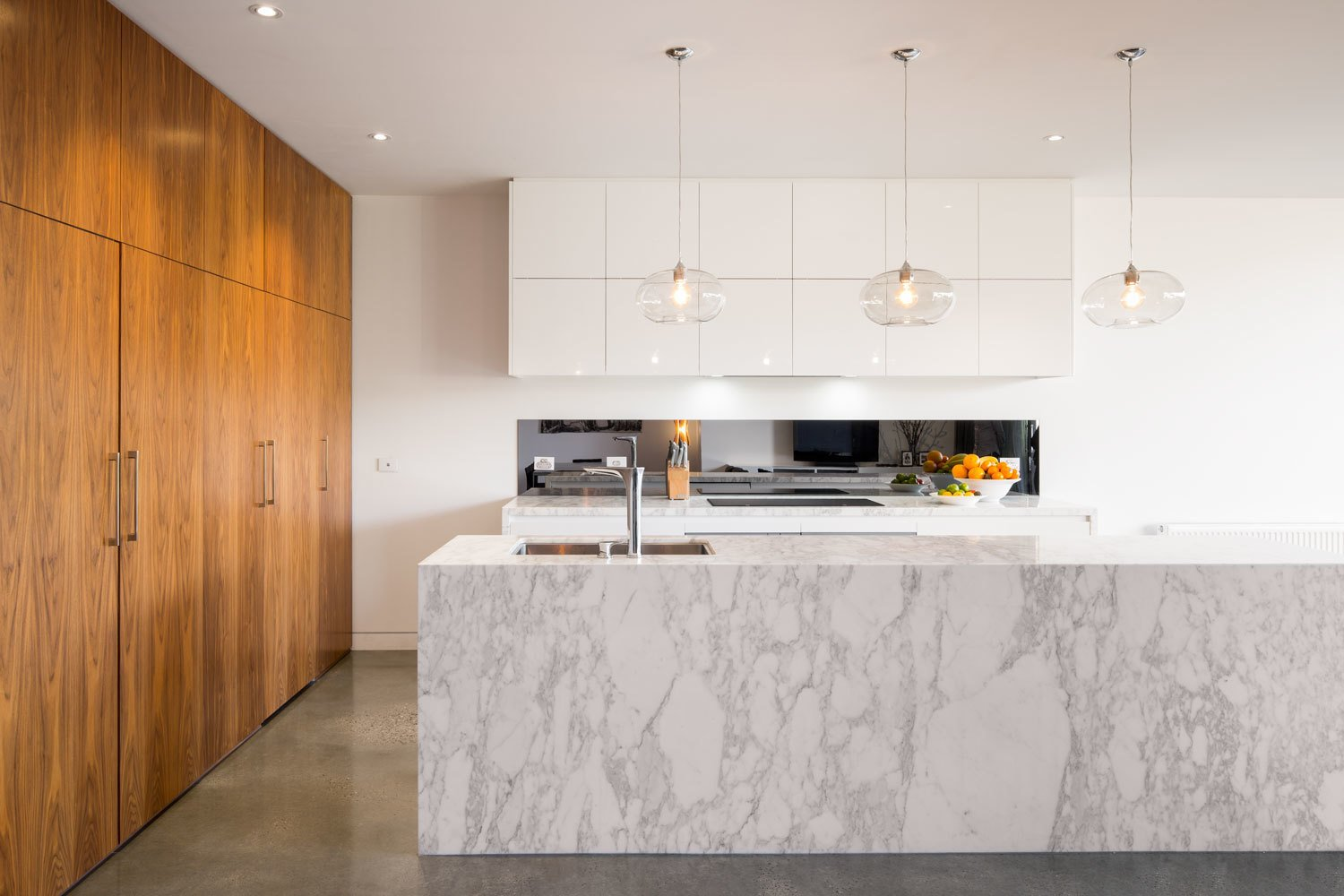 Kitchen, Marble Counter, White Cabinet, Concrete Floor, Wood Cabinet, Pendant Lighting, Undermount Sink, Recessed Lighting, and Cooktops The entire living and dining space features tough polished concrete floors. The architects intentionally contrasted the darker concrete and veneered pantry against the neutral white walls and marble. This color play runs through the renovated areas.  Photo 3 of 7 in Renovation: A Breezy Modern Addition Opens Up a Historic Melbourne Home from A Breezy Modern Addition Opens Up a Historic Melbourne Home