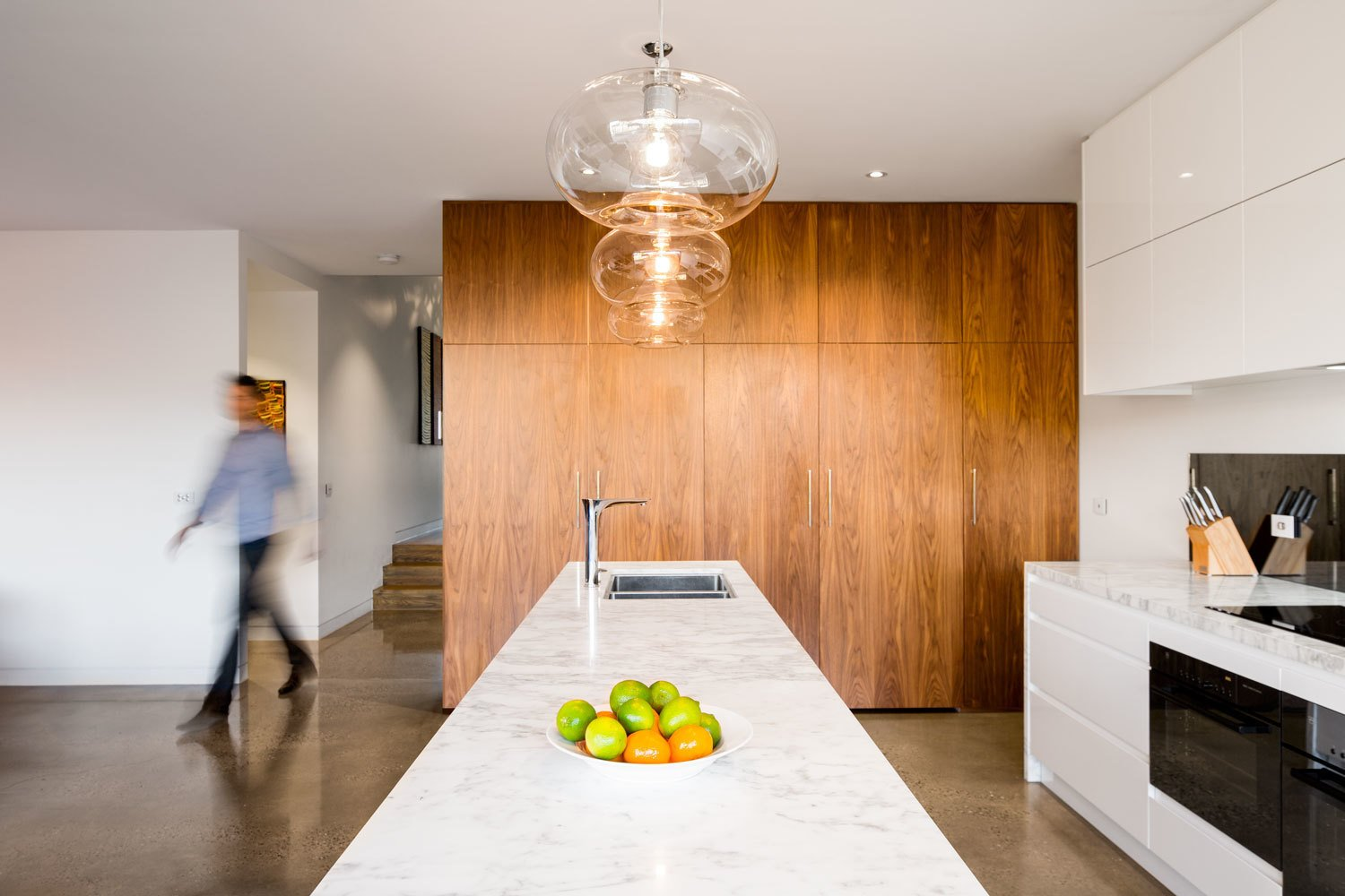Kitchen, Wood Cabinet, White Cabinet, Concrete Floor, Ceiling Lighting, Recessed Lighting, Wall Oven, Range, Pendant Lighting, Drop In Sink, and Marble Counter The feature lighting consists of incandescent bulbs encased in clear glass. Its brightness is complemented by spot lighting located along the room's perimeter.  A Breezy Modern Addition Opens Up a Historic Melbourne Home by Zachary Edelson