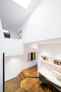 This double-height stairwell, just adjacent to the kitchen, marks the transition from the historic building to the new renovation. A skylight pulls sunlight from above into the home office below.