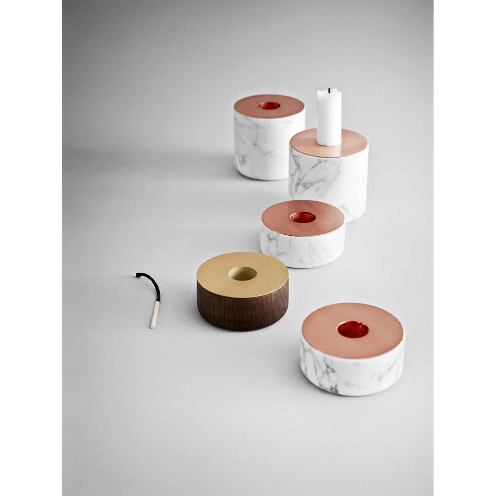 The aptly named Chunk Candleholder from Menu is a solid, substantial piece that looks purposeful and strong when set on a shelf or table. The cylindrical marble slab features a copper top, which counters the organic, raw nature of the marble with sophisticated shine. The result is a well-balanced accent that is an attractive decorative element whether it is holding a candle or resting on its own.   Available in two sizes: Large and Small.  Modern Candlestick Holders by Marianne Colahan