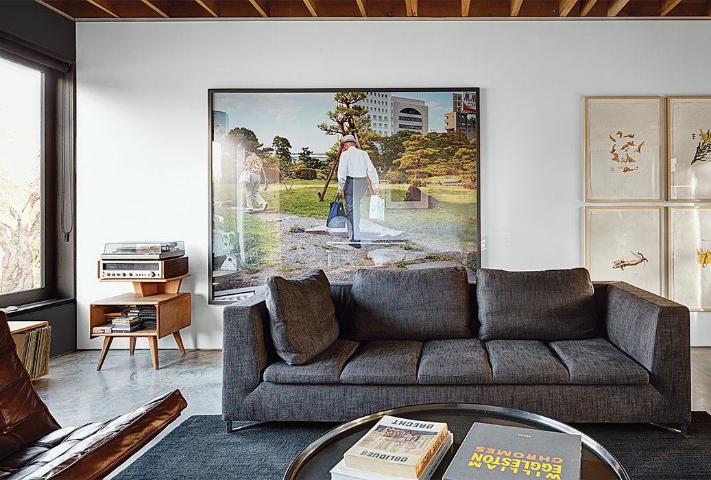 Living Room, Sofa, Coffee Tables, Chair, and Concrete Floor In the living area, a Ligne Roset sofa accompanies a vintage Adolf Loos coffee table. The 2003 photograph Pond Garden is by Stephen Waddell.  Modern Spaces in the Pacific Northwest by William Lamb