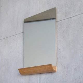Designed by Andrea Stemmer for SCP, the Jules Mirror is an unframed, rectangular portrait mirror that works well in a small-profile bathroom. The mirror features a solid oak storage shelf at its base, which can be used to hold small items including makeup, toiletries, or even favorite photographs and postcards. The shelf is made from a single piece of wood and is shaped like a half pipe, which counters the rigid straight lines of the mirror with a warm curvature.
