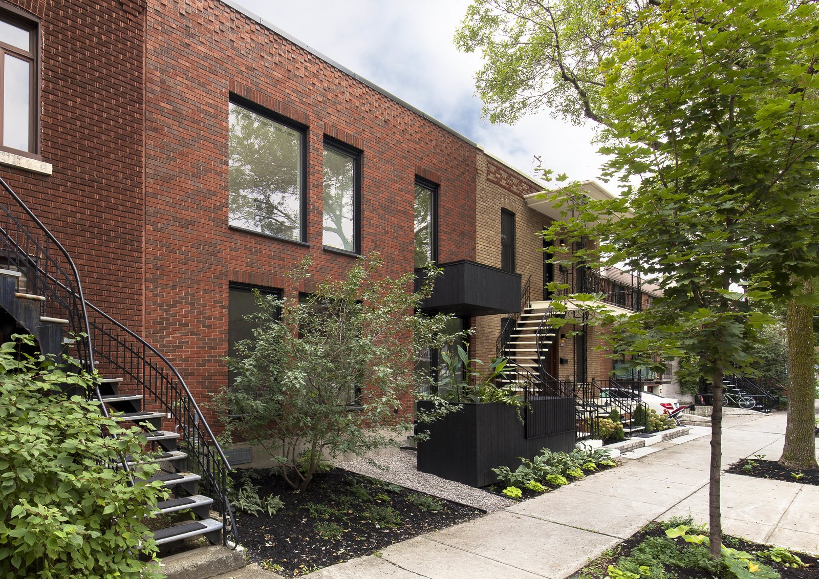 The architects chose dark-painted clay bricks for the facade, reasoning that it would complement the surrounding buildings. The windows were enlarged and oriented vertically.  Photo 14 of 15 in A Transformative Duplex Renovation in Montreal