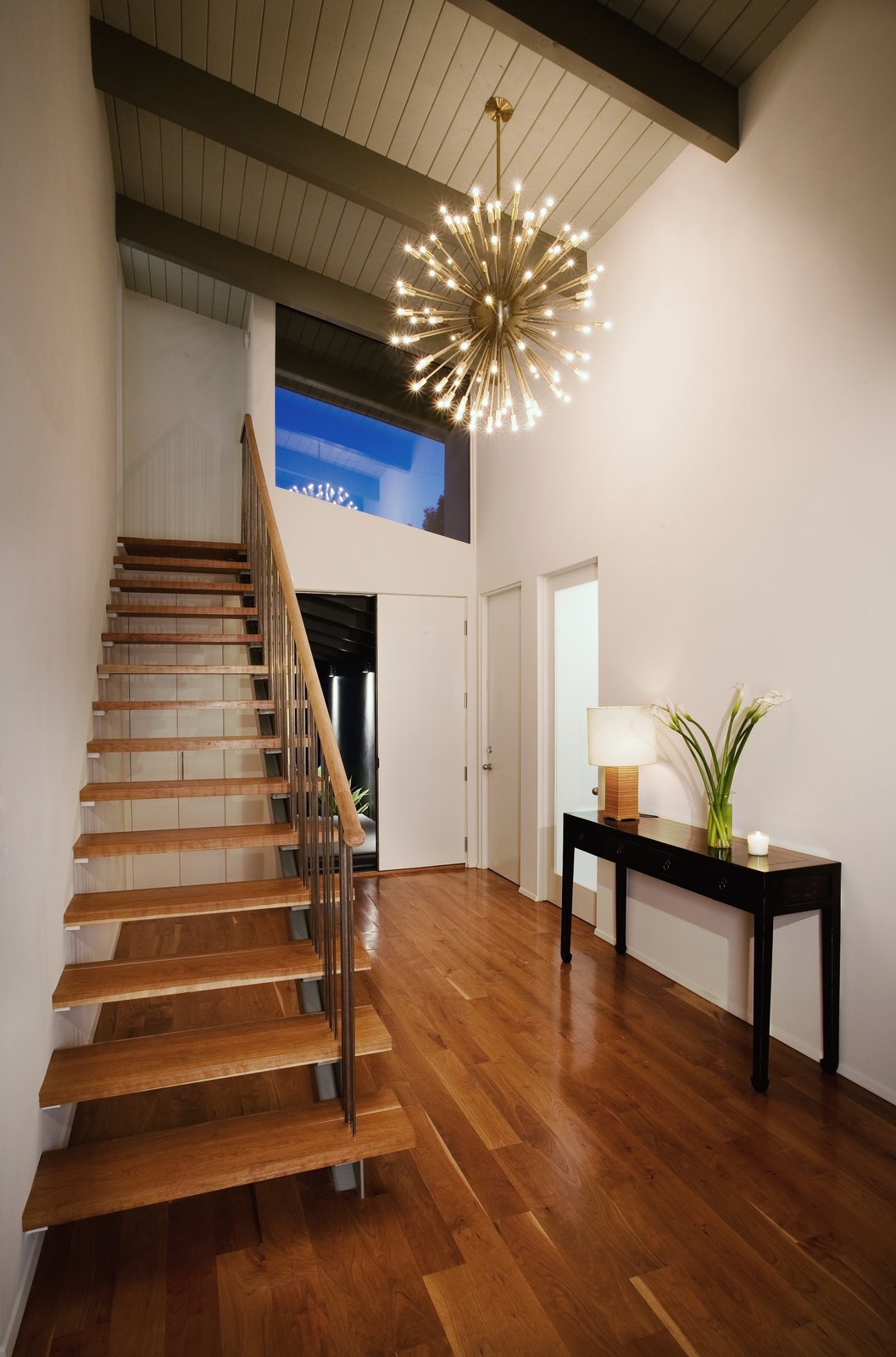 In the entryway, a brass Sputnik chandelier illuminates the airy American elm staircase.  190+ Best Modern Staircase Ideas from A Renovation Elevates This Humble Ranch Among its Iconic Midcentury Neighbors