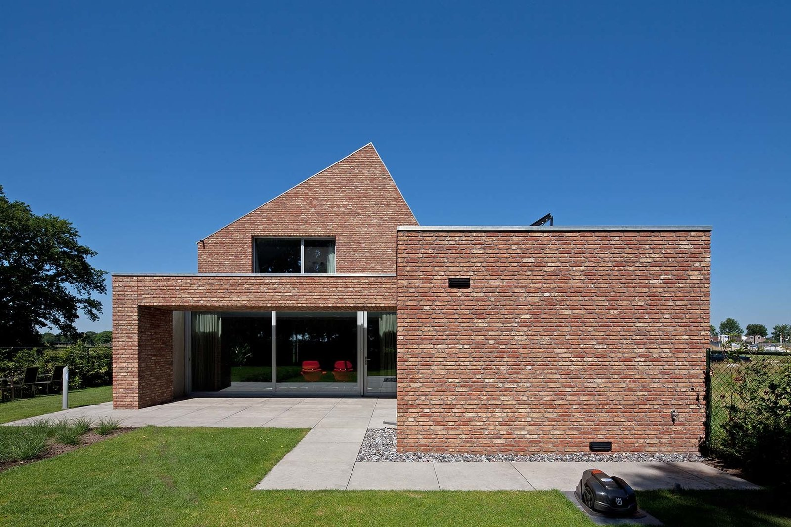 Grass, Back Yard, Exterior, Brick, and House It's traditional among homes in the region to enter through their backdoor, seen here. The door leads directly to the living room.  Best Exterior Brick Back Yard Photos from A Dutch Home that Plays with Traditional Brick Architecture