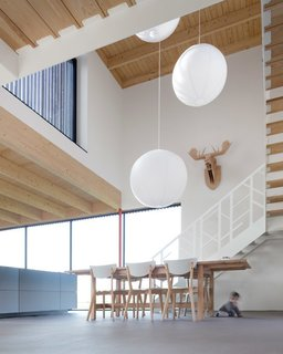 """""""All our kids moved out long ago, but now all the grandchildren stay over frequently,"""" Wilma said. """"The open space is great for them. They can bike and run around inside and with the walls of windows, we can keep an eye on them when they're outside."""" The stairs were custom made by Level Trappen, with a steel railing resembling interlaced branches from the nearby forest."""