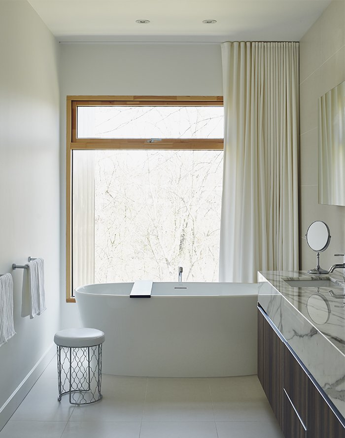 The master bathroom features Pro Tec windows framed in European pine, a freestanding tub by Wetstyle, and a marble vanity top from Ciot. Tagged: Bath Room, Freestanding Tub, and Wood Counter.  Modern Bathrooms by Allie Weiss from On a Peaceful Wooded Lot, a Futuristic Toronto Home is Buzzing with Smart Tech