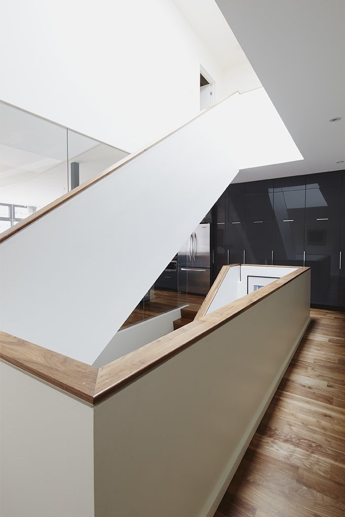 Staircase and Wood Tread In the kitchen, slate-gray Ikea cabinets and a KitchenAid refrigerator provide a sleek counterpoint to American walnut floors witha matte lacquer finish.  190+ Best Modern Staircase Ideas from An Architectural Mishmash in Montreal Becomes a Long-Term Family Home