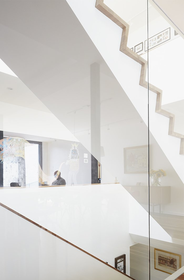 Staircase and Glass Railing Large windows by Alumilex and an operable Velux skylight—with built-in rain sensor to automatically close it in case of unexpected showers—flood the home with light. A glass wall surrounding the staircase reflects a chalk mural by artist Tyson Bodnarchuk.  190+ Best Modern Staircase Ideas from An Architectural Mishmash in Montreal Becomes a Long-Term Family Home