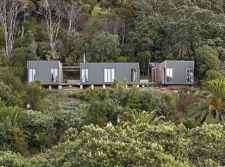 Located on the northern edge of Waiheke Island, approximately 800 feet from the nearest road, The Cora House sits atop a thicketed cliff that falls sharply into Hekerua Bayhe below. The prefab home's configuration maximizes views, while its siting limits environmental impact. Bonnifait + Giesen Atelierworkshop, the firm that designed the structure, was even able to retain the mature trees on the property.