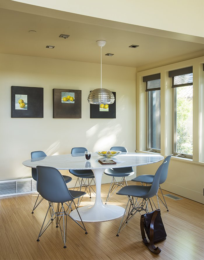 Dining Room, Pendant Lighting, Table, and Chair Inside the prefab residence, molded plastic Eames chairs from Design Within Reach rest beneath a Splugen Brau pendant light from Flos.  Photo 9 of 14 in A Homeowner Uses Smart Technology to Manage His Napa Property from Anywhere