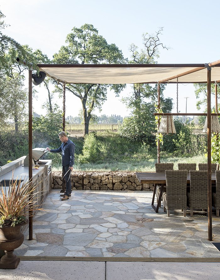 Outdoor, Large Patio, Porch, Deck, and Stone Patio, Porch, Deck An outdoor dining area is shaded by a mesh canopy suspended by old drilling pipes.  Photo 7 of 14 in A Homeowner Uses Smart Technology to Manage His Napa Property from Anywhere