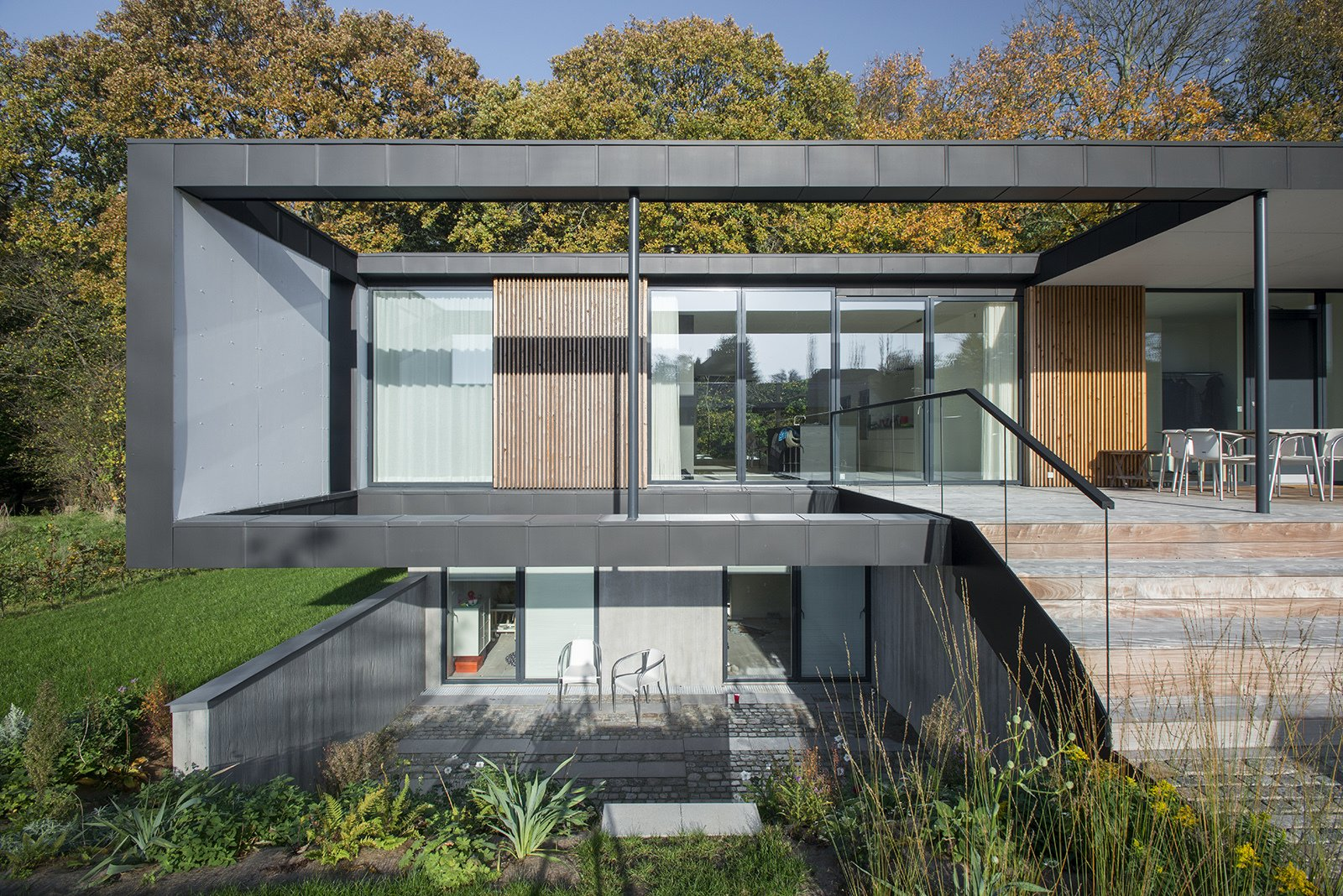 "Located in Aarhus, Denmark, Villa R is a minimalist, serene structure clad in zinc panels. ""The objective was to create a house that brings the forest inside through large glass panels—and create an ever-changing seasonal backdrop for the interior living spaces,"" stated the architecture firm, C.F. Møller, of the 3,200-square-foot abode.  Villa R by Diana Budds from Summer Getaways Amid the Trees"