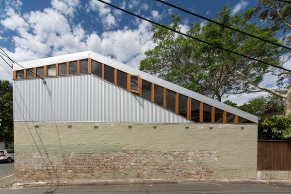 The architects designed the sloping roofline due to the existing jacaranda tree on the lot. Foliage used to collect on the old roof, clogging the gutters. The new structure's dramatic pitch prevents leaves and branches from accumulating.