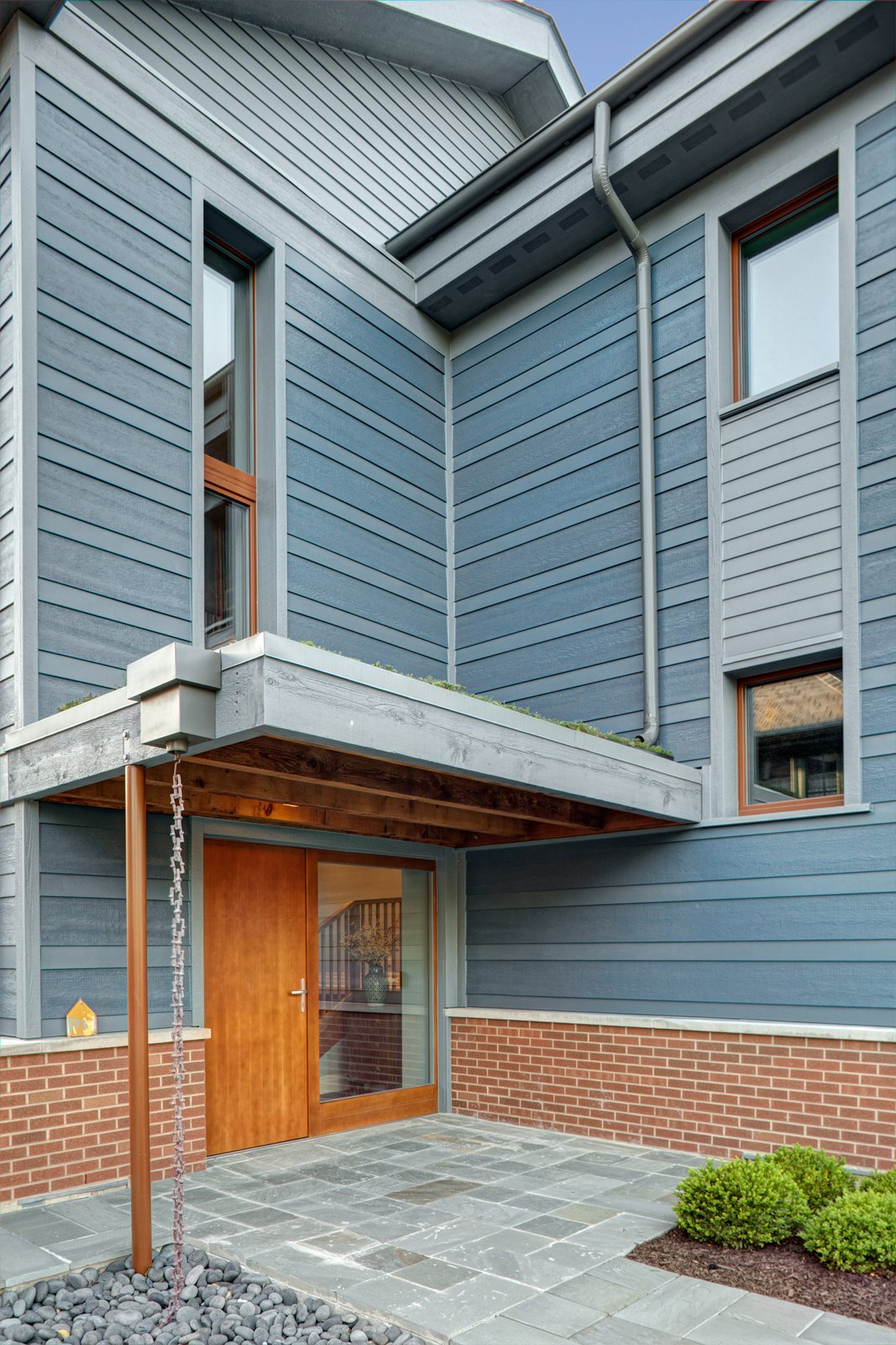 The entry sequence was designed to allow accessible entry, creating a sense of shelter and highlighting the thickness of the super-insulated ICF walls.  Photo 2 of 8 in Sustainable Living: Chicago's First Certified Passive House