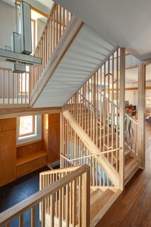 The American Yellow Birch-clad staircase was designed as a screen inspired by light filtering through a forest.  Photo by: Eric Hausman Photography