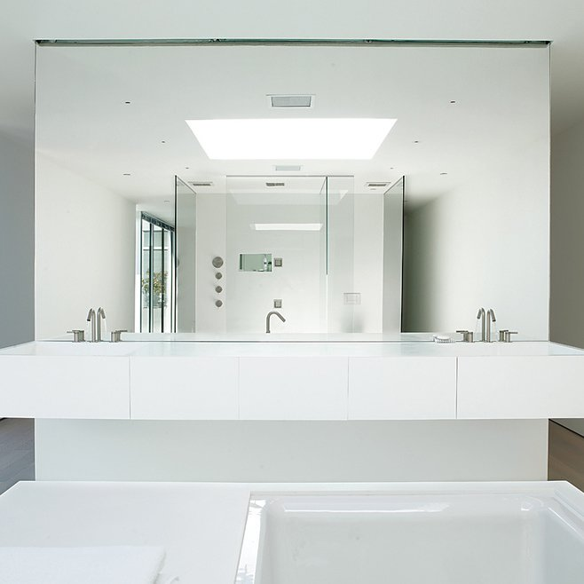 """In the penthouse apartment in 1234 Howard, a 17-unit residential structure in San Francisco designed by Stanley Saitowitz, the master bathroom is outfitted with Kohler fixtures and custom pieces. According to Saitowitz, an austere palette helps occupants bring in more of their personal touch: """"The basic approach is to create a quite neutral type of palette, so that the occupants can determine the style by the way they select their furnishings. It's like creating a blank canvas, where they can actually enhance the character by the way they inhabit their space."""" Photo by Dwight Eschliman.  Week in Review: 7 Great Stories You May Have Missed September 6, 2013 by Megan Hamaker from Luxurious All-White Bathrooms"""