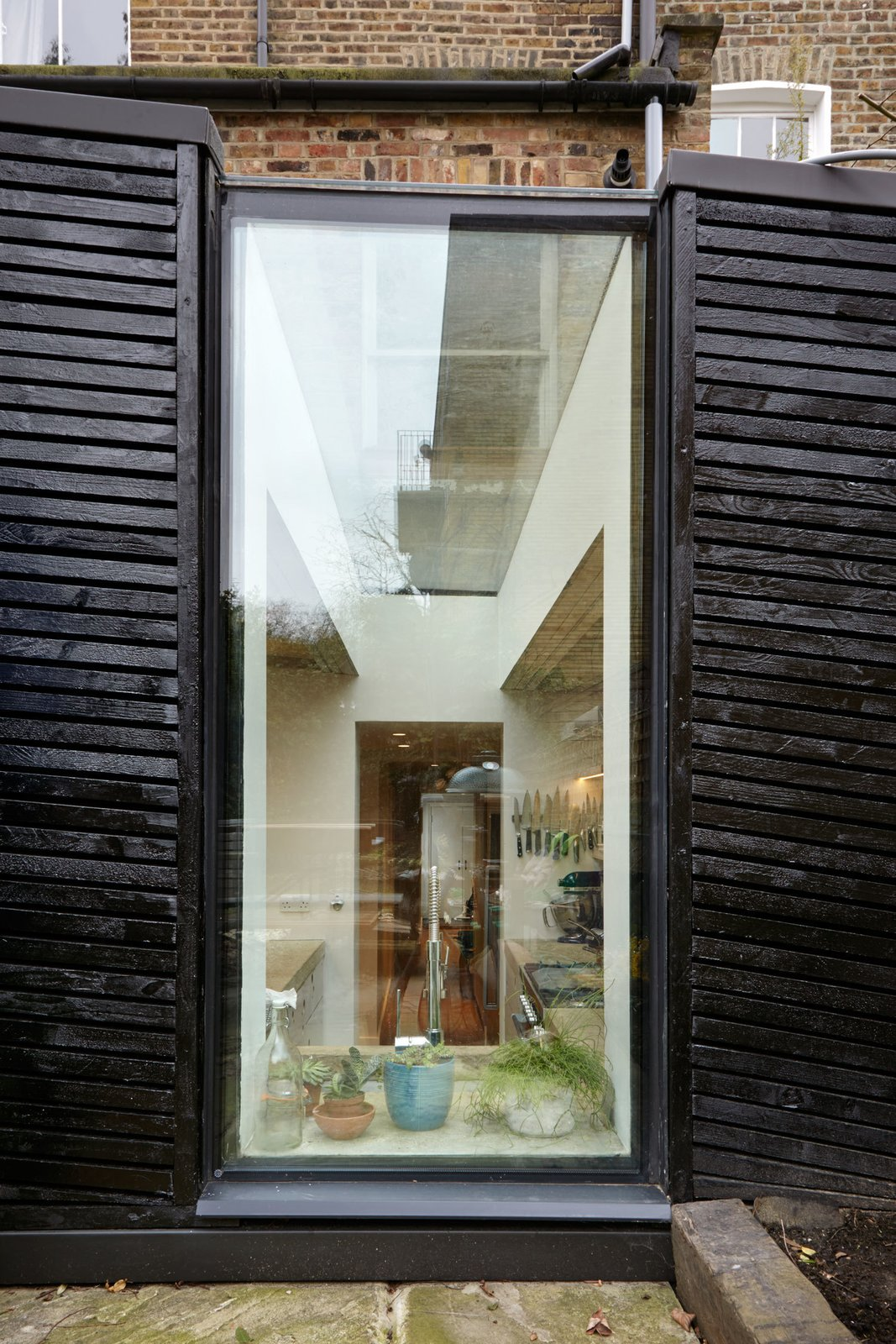 The kitchen enjoys plenty of natural light, thanks to a narrow glass window above the kitchen sink that effectively continues onto the roof as a skylight.  A Modern Addition Gives a London Chef a Dream Kitchen by Laura C. Mallonee