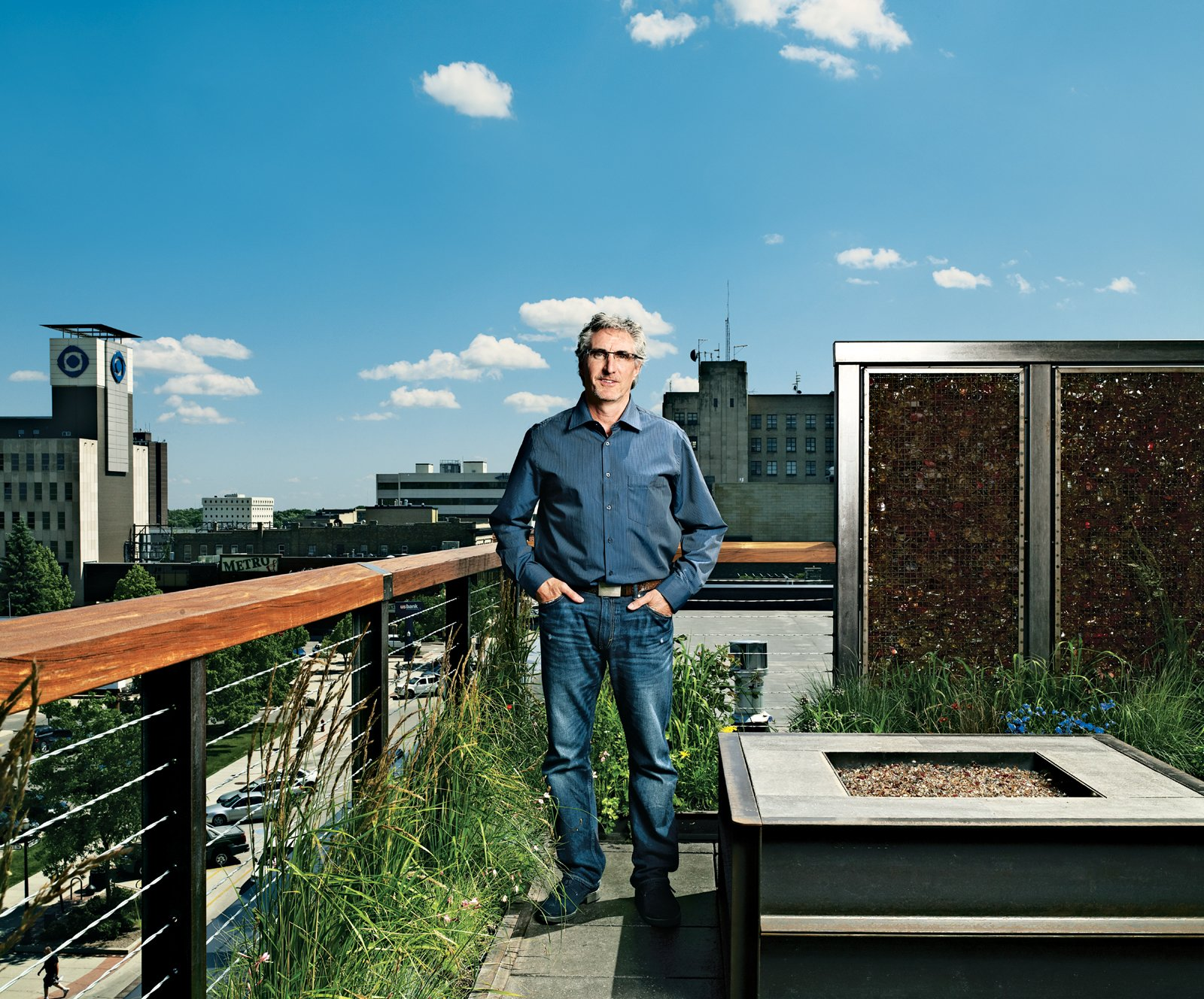 Fargo native son Doug Burgum stands on his rooftop deck. Landscape architect Brian Reinarts outfitted the space with local grasses and plants, LED-illuminated privacy screens, and a natural-gas fireplace.  Photo by: David Bowman  Photo 1 of 6 in Green Planning in North Dakota