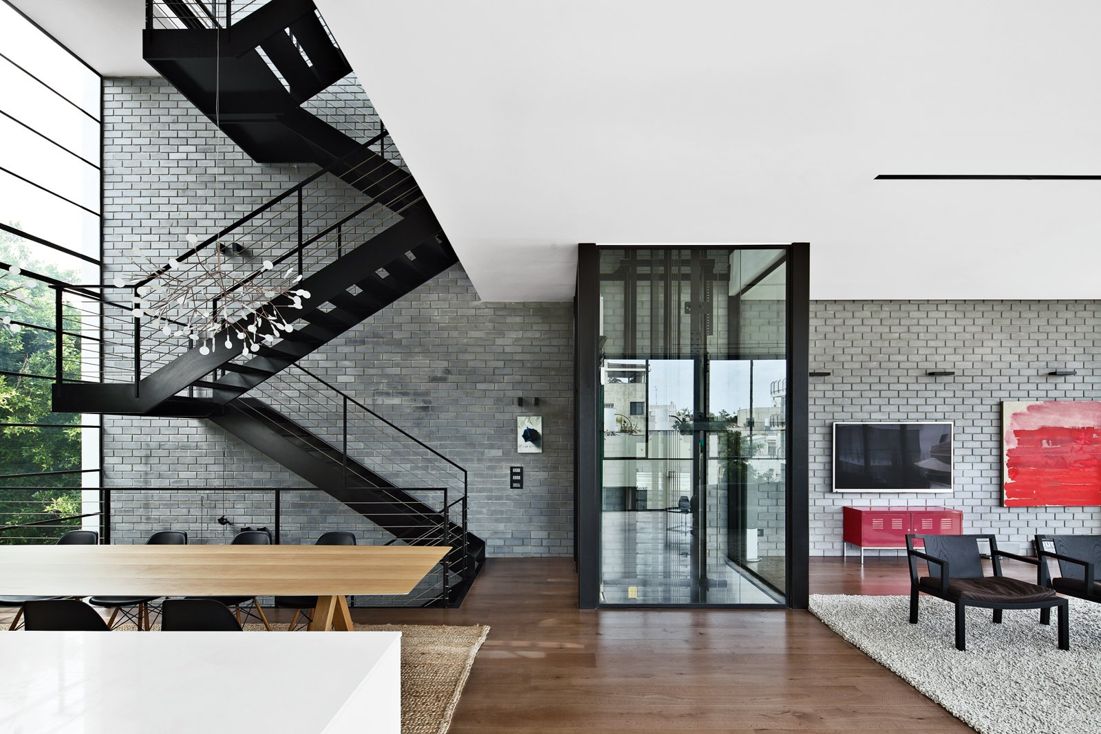 Living Room, Chair, Medium Hardwood Floor, and Rug Floor The residents use either the black steel staircase or a glassed-in elevator by Wittur to get around the house.  Inspiratie nieuw huis from Modern High-Rise Town House in Tel Aviv