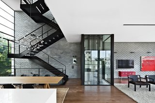 The residents use either the black steel staircase or a glassed-in elevator by Wittur to get around the house.