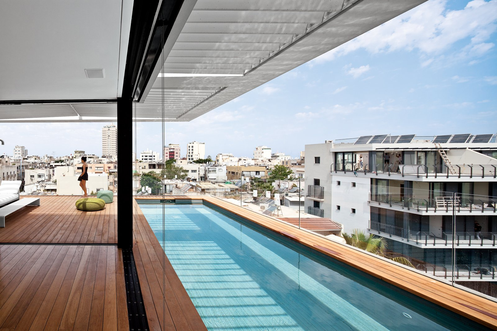Outdoor, Swimming Pools, Tubs, Shower, Lap Pools, Tubs, Shower, Rooftop, Wood Patio, Porch, Deck, and Large Patio, Porch, Deck The decking on the rooftop is Burmese teak and the colorful Picot pouffes are by Paola Lenti.  Photo 8 of 8 in Modern High-Rise Town House in Tel Aviv