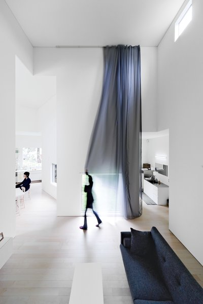 A sheer curtain screens the living room from the outside.