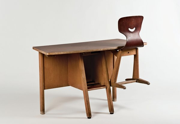"Fritz Flötotto   The Formsitz chair, developed by the company Flötotto for German schools in 1956, features a patented seat made of ""pagwood"": beech veneers soaked in resins and treated to develop characteristics of plastic. (A contemporary polypropylene version of Fritz Flötotto's original chair was designed for the company in 2012 by Konstantin Grcic.) For efficient classroom sweeping, the Formsitz chair slides into brackets on the underside of the corresponding wood desk, also from 1956."
