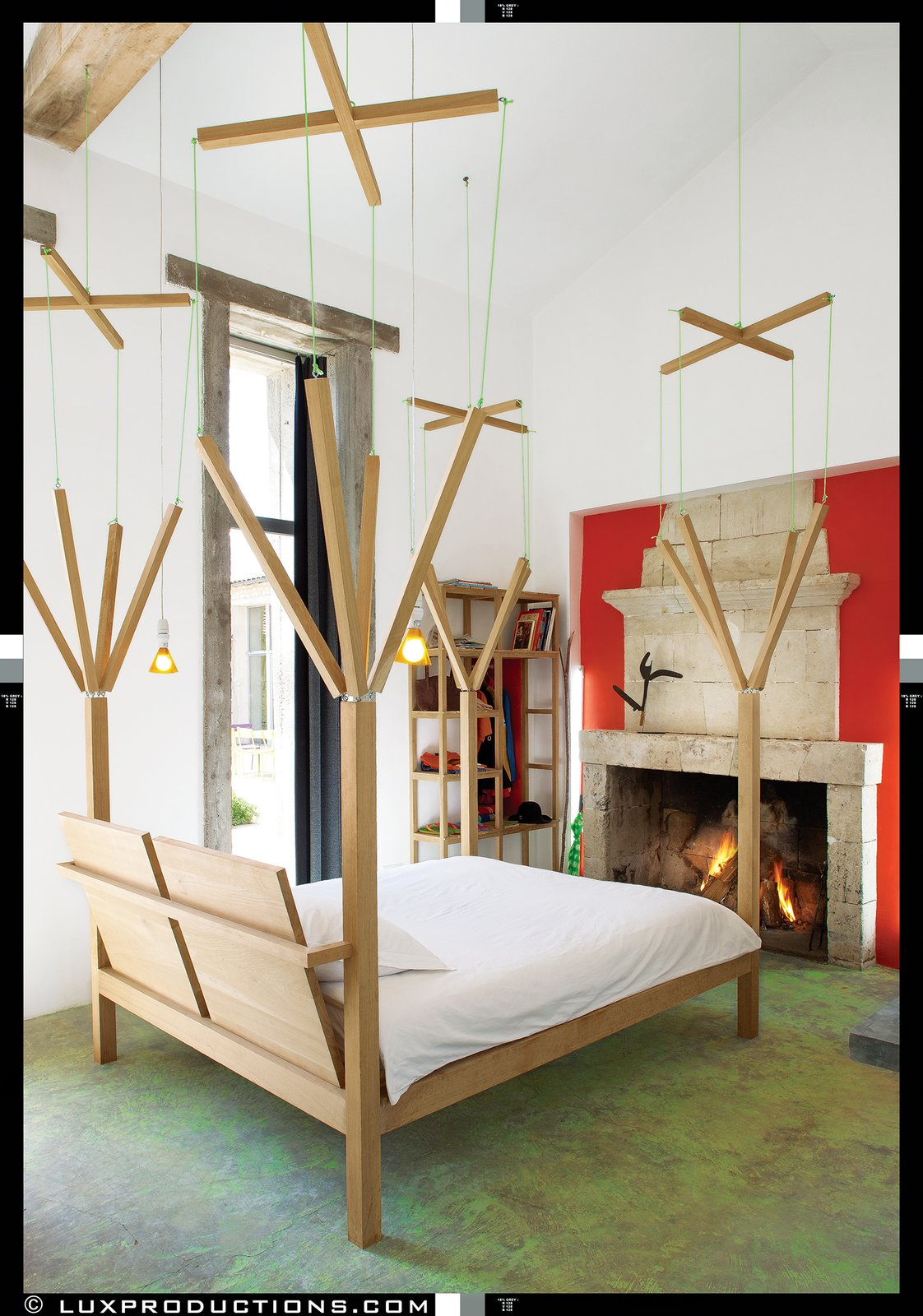 All of the beds in the house are playful custom one-off designs by Crasset, including the marionette-themed master bed, which a local carpenter fabricated from oak felled in the surrounding forest. The stone fireplace is original.  Bedroom from Matali Crasset Renovates Monory Farmhouse