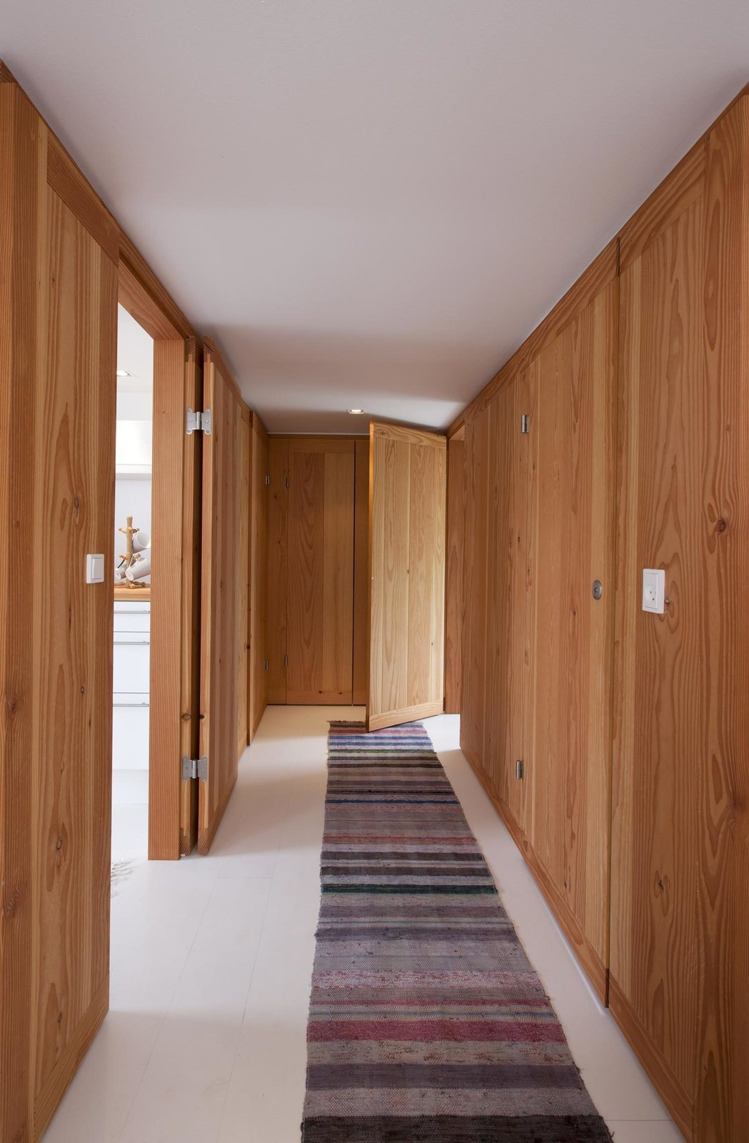 Hallway Douglas fir lines the walls of the entryway. A narrow striped rug adds texture to the white-painted wooden floor from Dinesen.  Best Photos from A Thatched Cottage in Denmark with a Modern, Space-Saving Interior