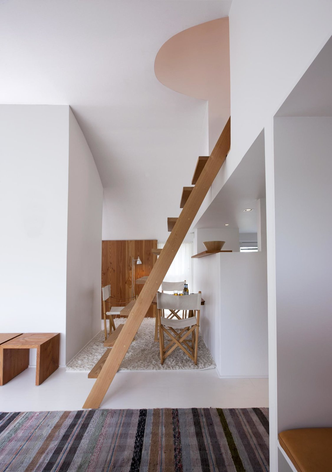 Staircase and Wood Tread A small dining room occupies the space just beyond the living room. It's furnished with vintage folding chairs designed by Danish architect Mogens Koch that are easily stored for more space.  D e n m a r k from A Thatched Cottage in Denmark with a Modern, Space-Saving Interior