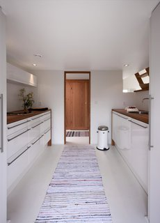 The kitchen cabinets and fixtures are all sourced from Swan Cuisines. The trashcan is by Vipp. The architects opted to install only a small stove with no oven, as the garden already has a fireplace.