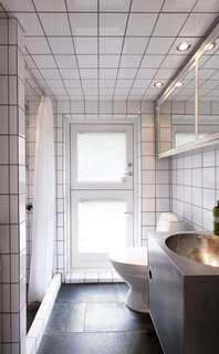 In the bathroom, plain white tiles line the walls and ceiling. The floors are natural stone and the fixtures are by VOLA. Lassen built the sink himself.