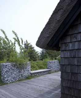 "A modern stone fence made of galvanized steel mesh filled with stones surrounds the house. ""We got the stones from the local stonecutter—they use the stones washed up on the beach, not the stones from the fields,"" Lassen explains."