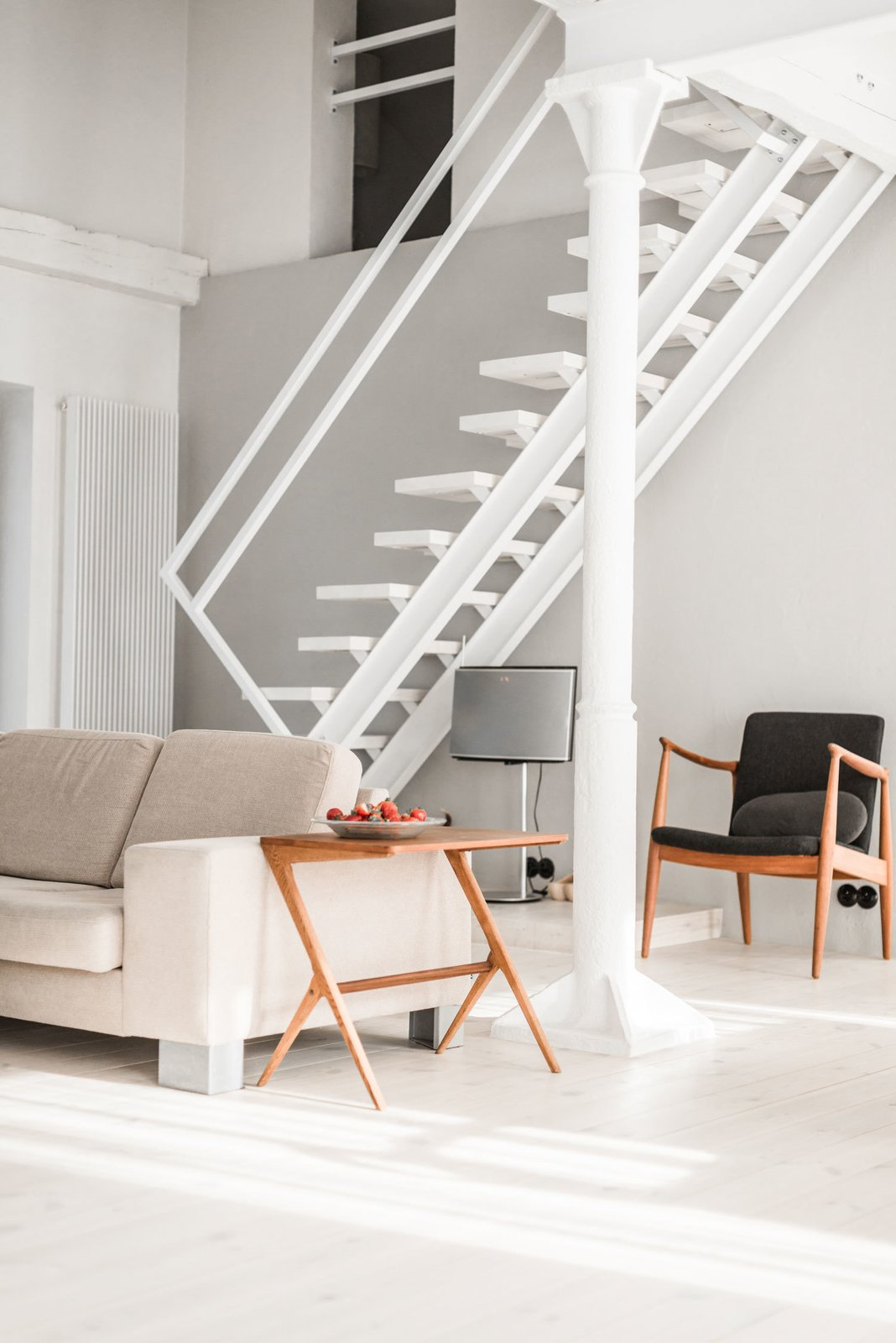 "Living Room, Sofa, and Chair The designer took his inspiration for the minimal staircase from traditional Polish ""duck stairs."" Since they're narrow, they're ideal for smaller spaces. The couch was purchased from BoConcept.  Photo 3 of 10 in A Run-Down Farmhouse Becomes a Sleek Modern Retreat"