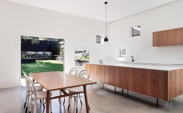 The custom kitchen cabinets sit on legs for easy sweeping underneath. They're topped with white Corian counters and paired with sleek Brodware fixtures.