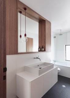 Modern bathroom vanities in white bathe the room in light, creating a relaxing atmosphere. Mirroring the kitchen of this home, the bathroom features custom wooden cabinetry and Brodware faucets.