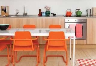 #1: Paint it...orange. In this custom-built London guesthouse kitchen designed by Studiomama, lustrous vertically clad cabinetry achieves additional depth with the addition of the chairs, which were picked up for $15 each at a local market and powder coated in bright orange.
