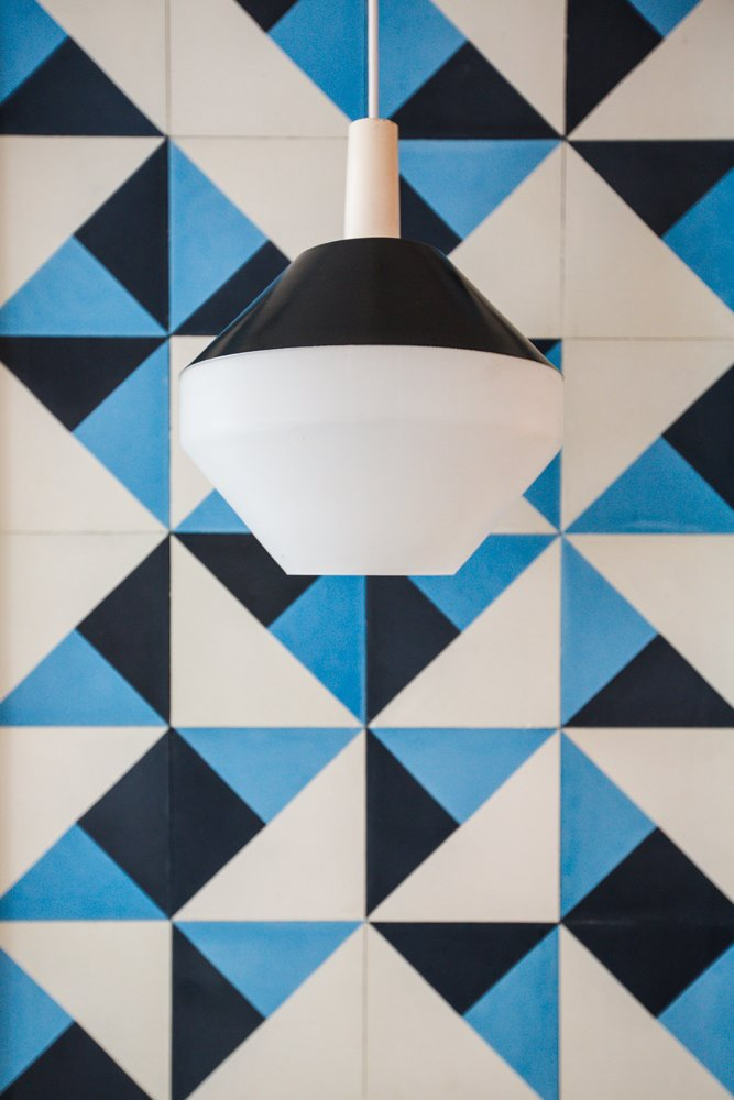 The pendant, sourced from Amsterdam Modern, is made from Black spun aluminum and vintage Pilastro Diamond milk glass.  Pattern from A Bright, Geometric Bathroom Renovation in Los Angeles