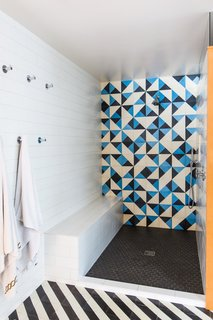 The shower is flanked by walls covered in Dal Tile in Arctic White.