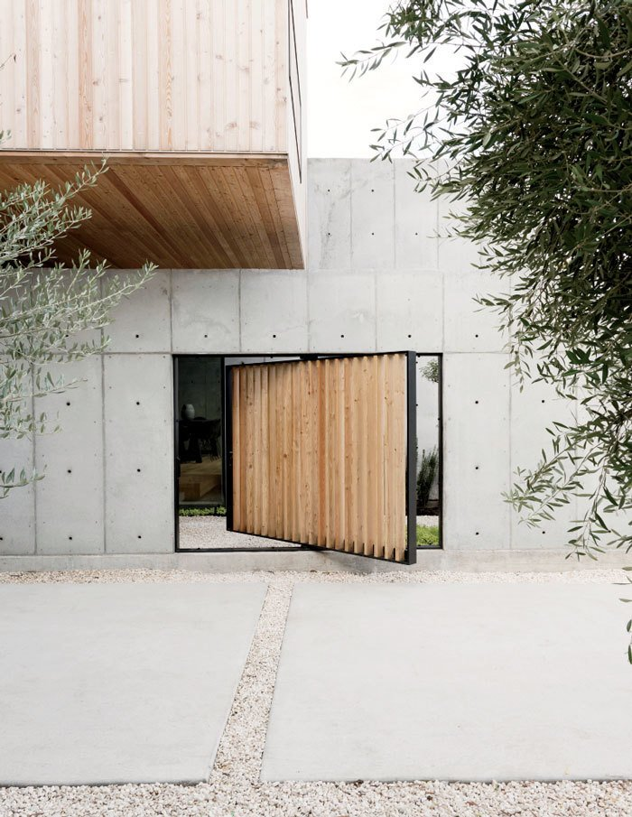 Doors, Wood, Exterior, and Swing A pivoting door, also made of larch, provides a shortcut to enter the structure as an alternative to the main courtyard entrance.  Best Doors Photos from A Texas Couple Builds Their Cast-In-Place Concrete Dream Home