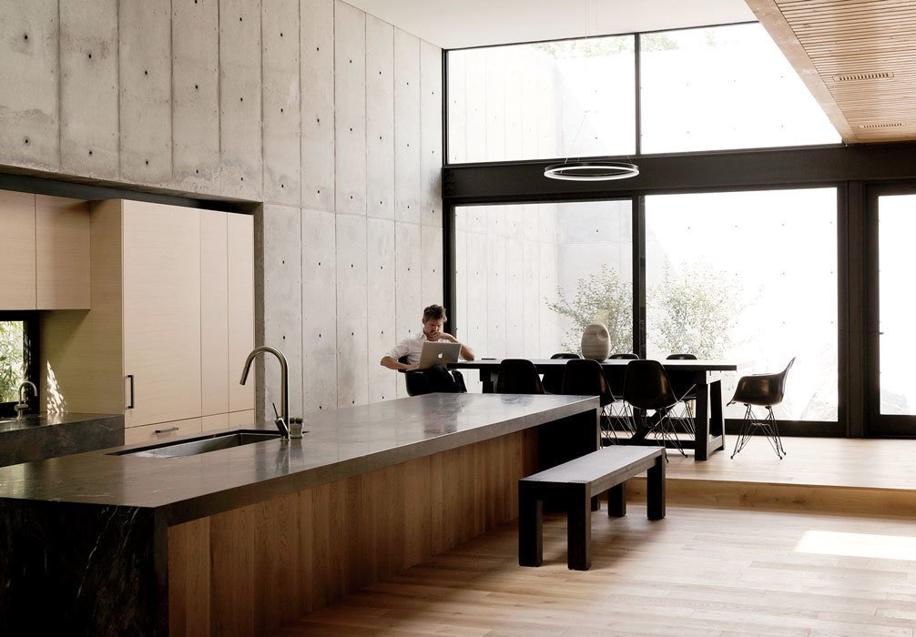 Concrete Box House kitchen and dining area with concrete walls and wood floors.