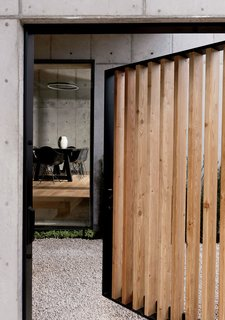 """We talked about creating a sense of mystery when [guests] walked in from the street,"" says Christopher. A gate swings open on a steel bar-stock frame to reveal a courtyard and the dining room beyond."