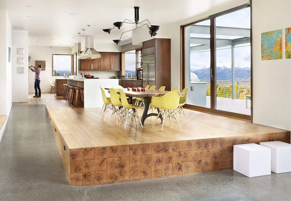 Dining, Stools, Bar, Chair, Storage, Table, Shelves, Ceiling, Pendant, and Recessed Beams extending from the kitchen floor give the impression of an oversize butcher-block stage for a custom walnut-slab table and a dozen Molded Plastic chairs by Charles and Ray Eames for Herman Miller.  Best Dining Shelves Table Bar Recessed Stools Photos from A Custom, LED-Lit Slide Twists Through This Family-Friendly Vacation Home